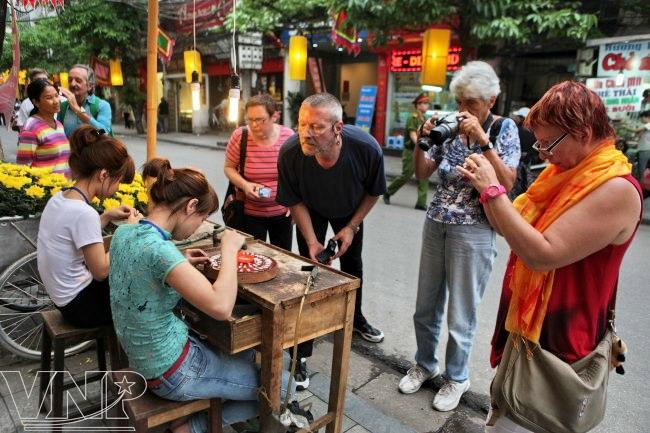 On peut voir les gens travailler en rue Hang Bac
