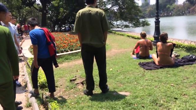 2 touristes étrangers en bikini lors de leur bronzage au bord du lac Hoan Kiem