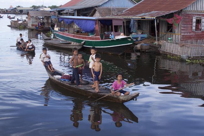 Enfants en bateau dans un village sur le lac de Ton Le sap